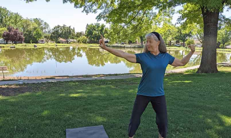 """a woman doing the """"bow"""" tai-chi pose while standing on the lawn in front of a lake"""